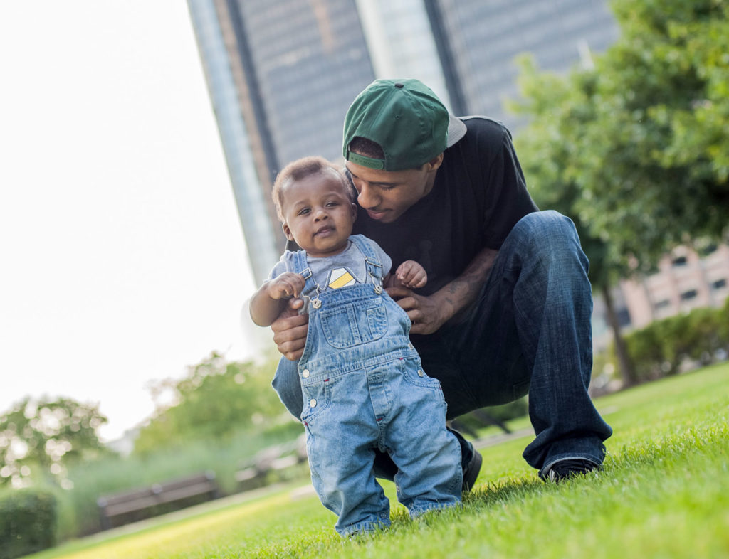 father helping his toddler take steps