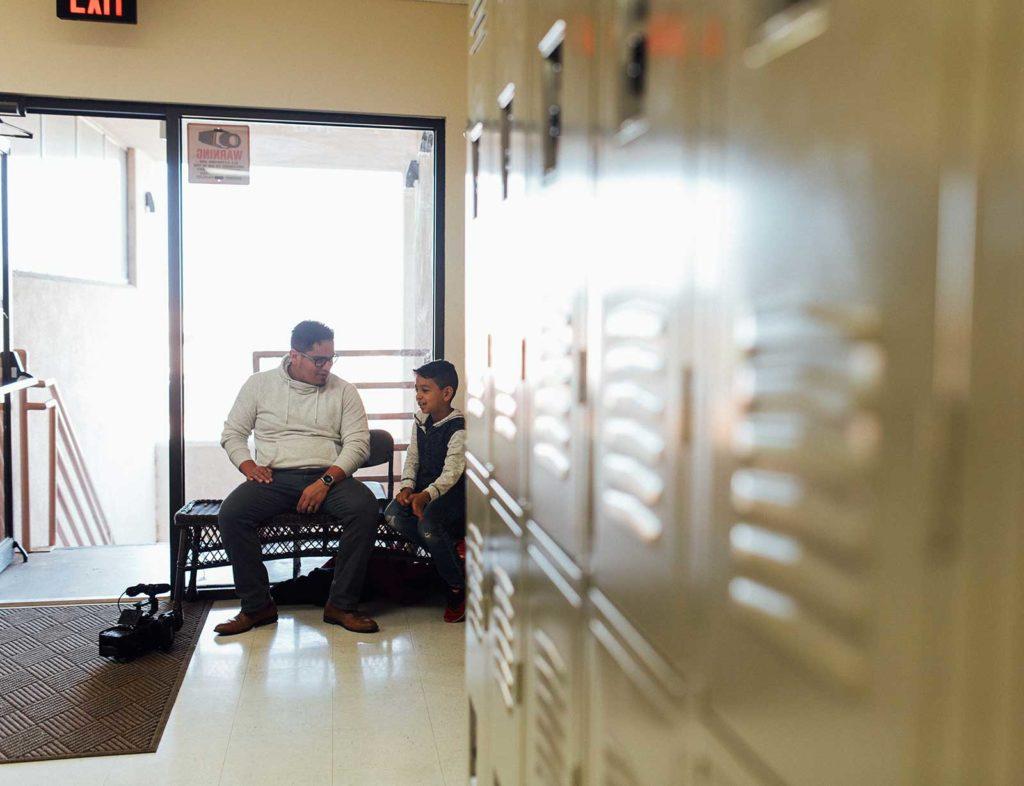 teacher and student sitting in school hallway